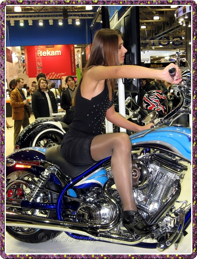 Long haired model in black boots on motor bike