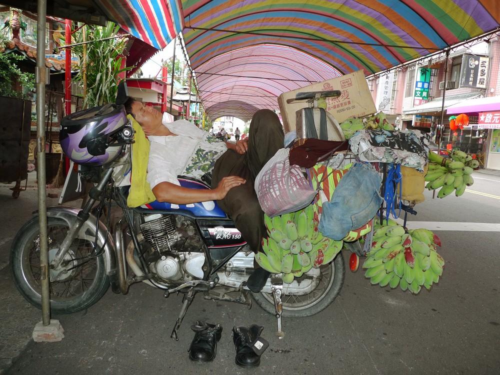 man sleeping on motorcycle in taiwan