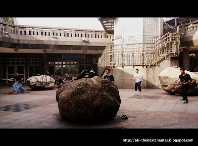 Dancers practising a dance, stick in hands. Big boulder in the middle of the square.
