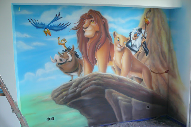 Malowanie na ścianie motywu z kultowej bajki Król Lew, ciekawy sposób na zaaranżowanie ściany w pokoju dziecięcym