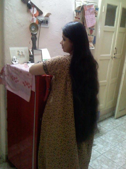 long hair women opening refrigerator.