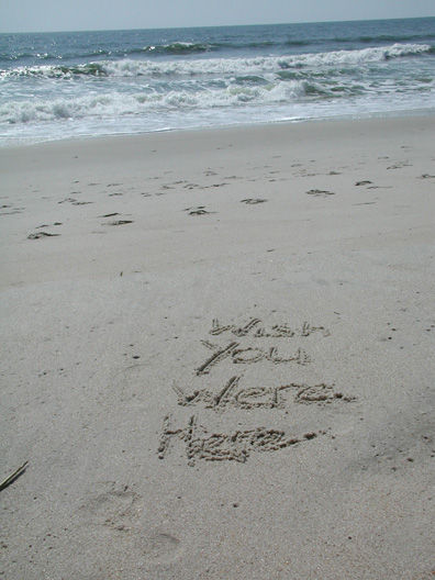 I wish you were here written in beach sand
