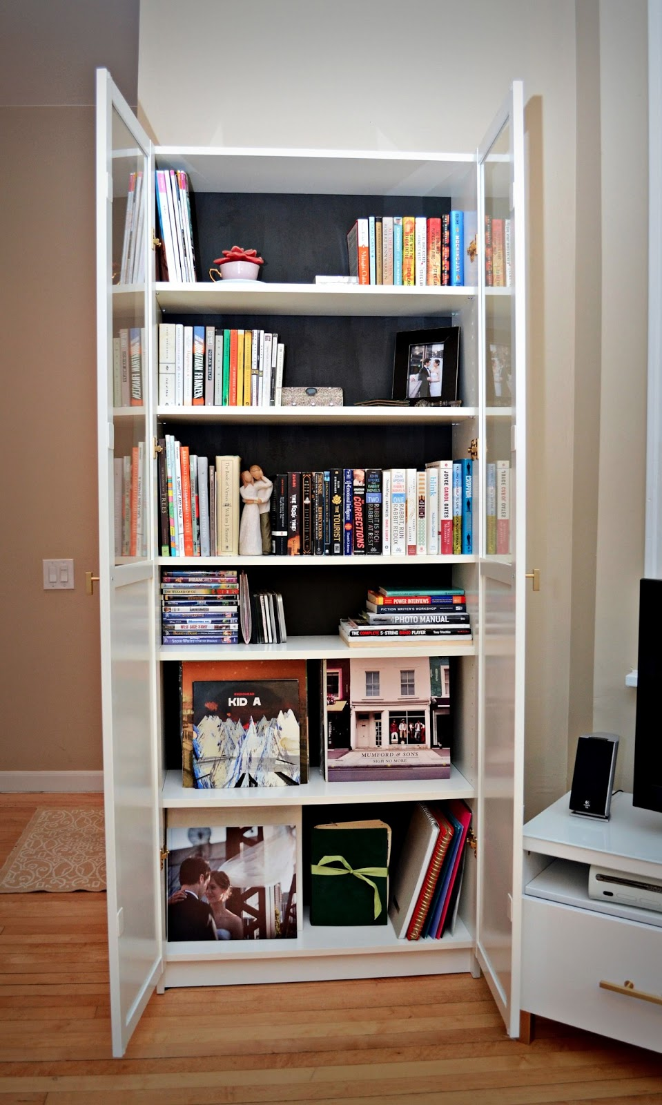 Billy Bookcase Doors Hack :  we paired it with glossy white doors and topped it with white glass