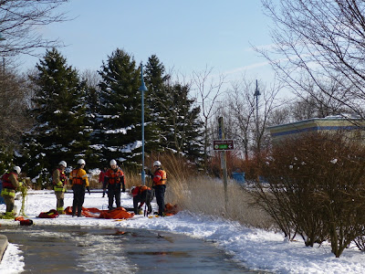 Group of firemen in safety gear inflate rescue boat at Port Credit Marina near Snug Harbour.