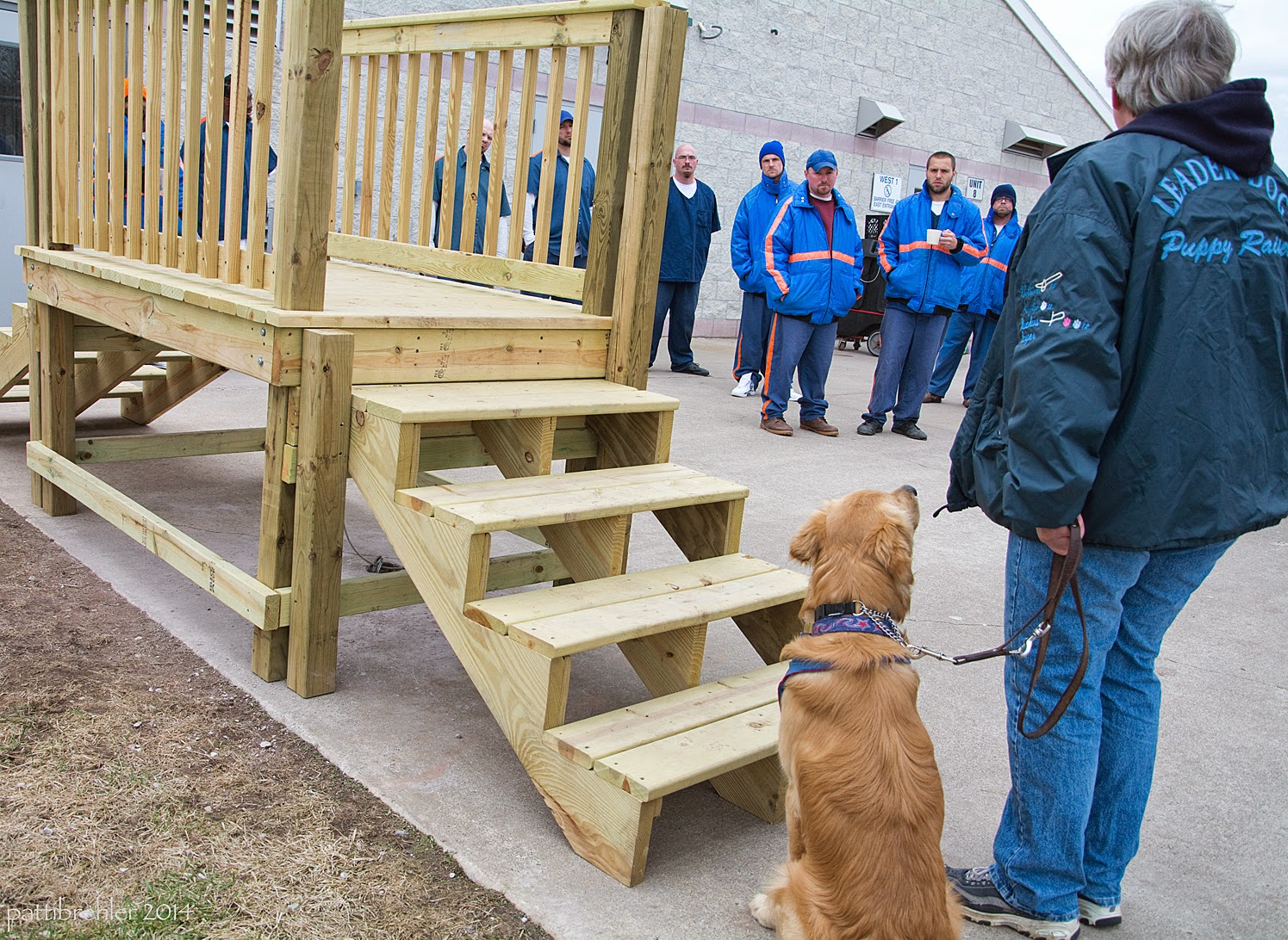 The same woman is more visible on the right side of the picture. Now her left hand is at her side holding the leash loose, and the golden retriever is sitting at her left side, looking up at her. There are more people in the background. On the left is the wooden stairs up to a platform and down the other side.