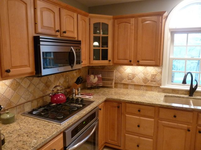 Countertops: Ouro Brazil Granite. Backsplash: Mojave Tumbled Travertine.  Cabinets: Maple With A Natural Finish. Sink: Blanco Silgranit In Biscotti