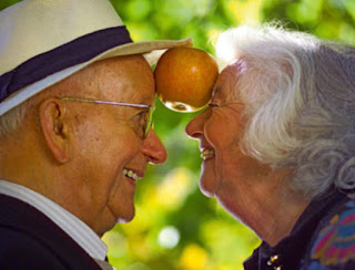 Ein älteres Paar hält einen Apfel zwischen ihren Stirnen und lächelt sich an