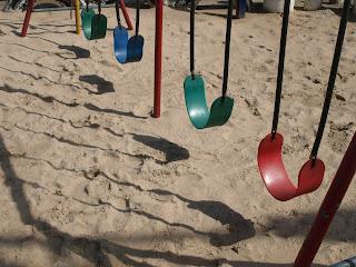 cuatro columpios de colores, sobre un suelo de arena de playa
