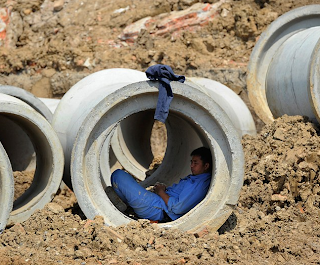 funny pictures: Chinese worker sleeping in the concrete pipe