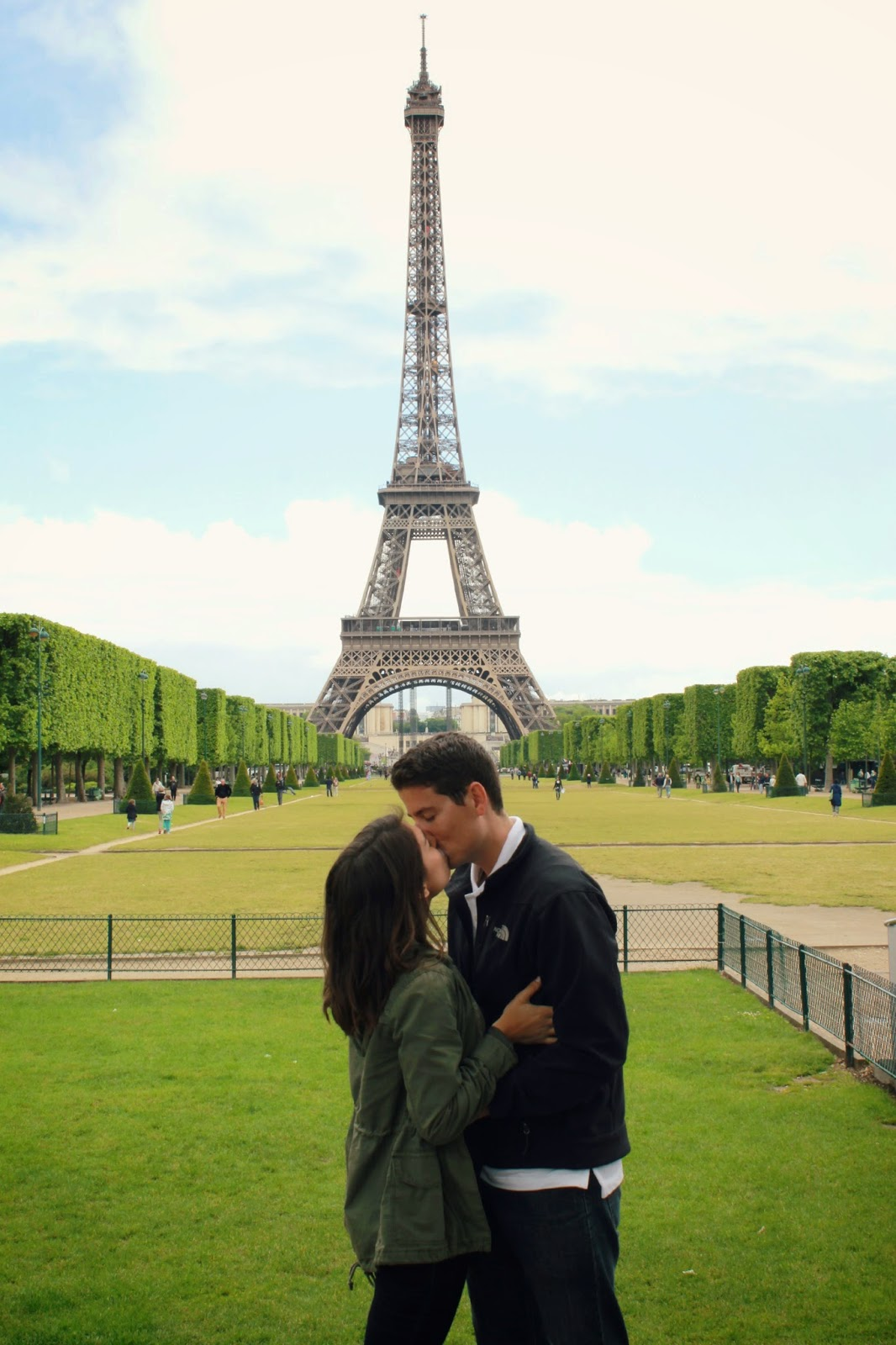 A couple kissing in front of the Eiffel Tower in Paris, France.