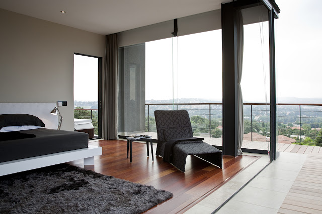 Picture of black and white furniture in the bedroom with glass walls