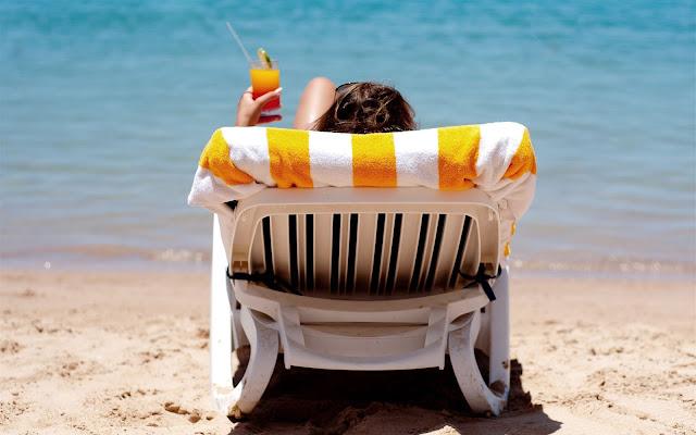 Vrouw op een ligstoel op het strand bij de zee