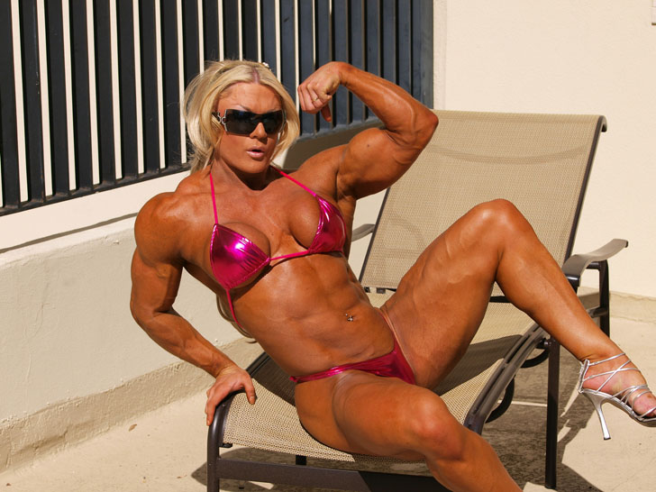 Lisa Cross Flexes And Models Her Muscles In A Fuchsia Bikini
