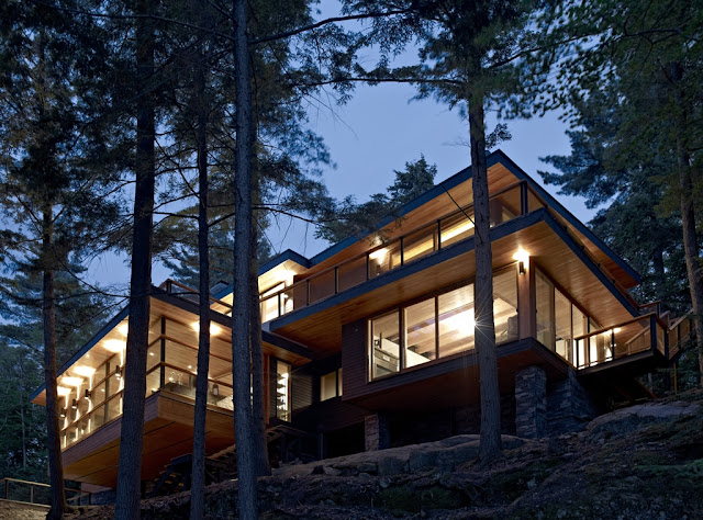 Photo of the forest house built on the hilly terrain at sunset