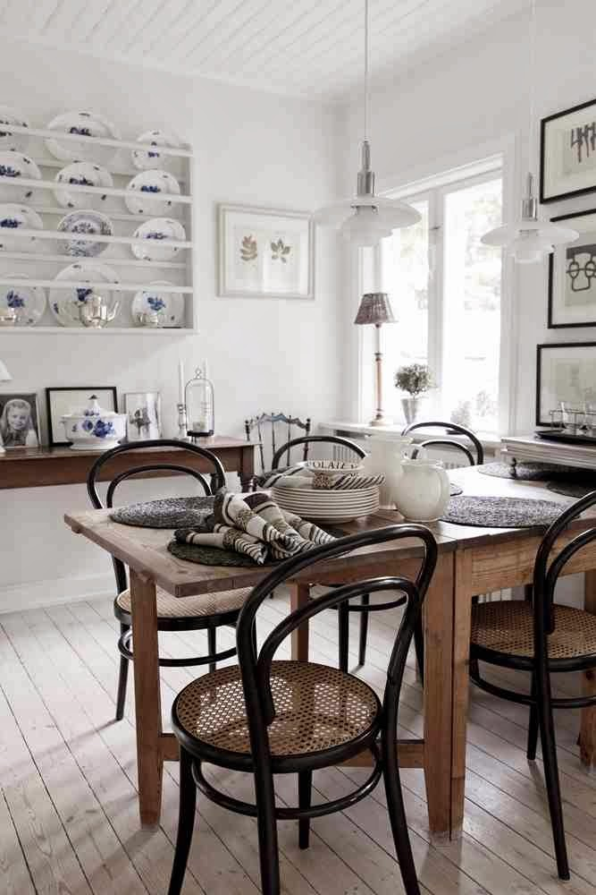 Sielski styl kuchni, białe ściany biała podłoga, drewniany stół, białe talerze z niebieskim wzorem na otwartej półce
