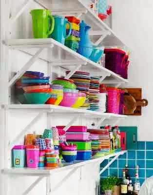 Kolorowe naczynia na białych półkach w kuchni