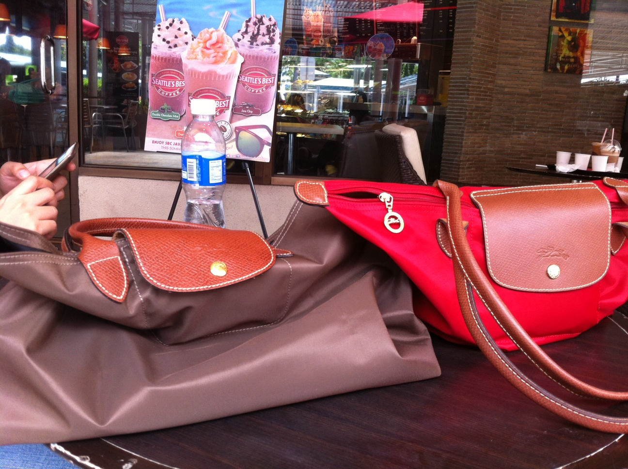 The two Longchamp bags look the same at first glance, but the plastic  material feels different - the brown bag feels slightly coarser, more  durable.