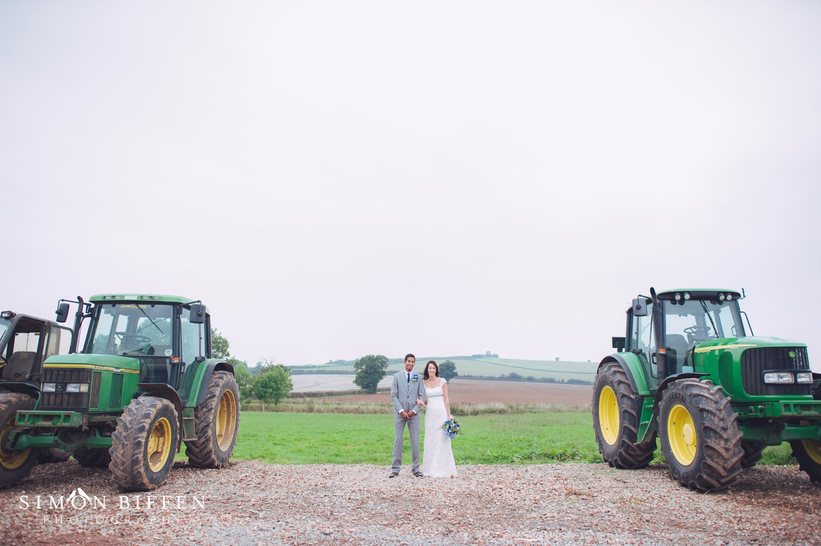 Bride and groom with tractors at Quantock Lakes wedding