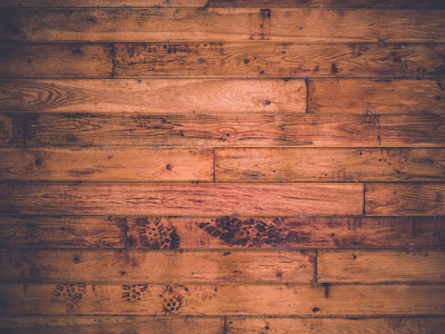 horizontal image of a wooden floor with shoe prints