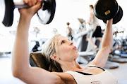 . No hay diferencia entre hombres y mujeres para entrenar en un gimnasio. (woman lifting free weights in fitness gym assembly)