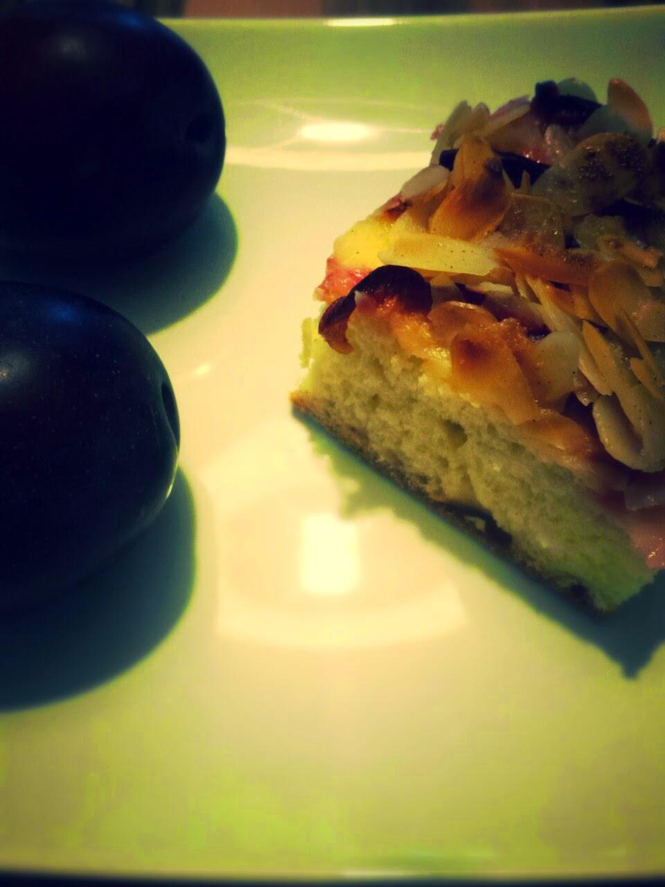 Zwetschgenkuchen auf einem Teller mit zwei Zwetschgen