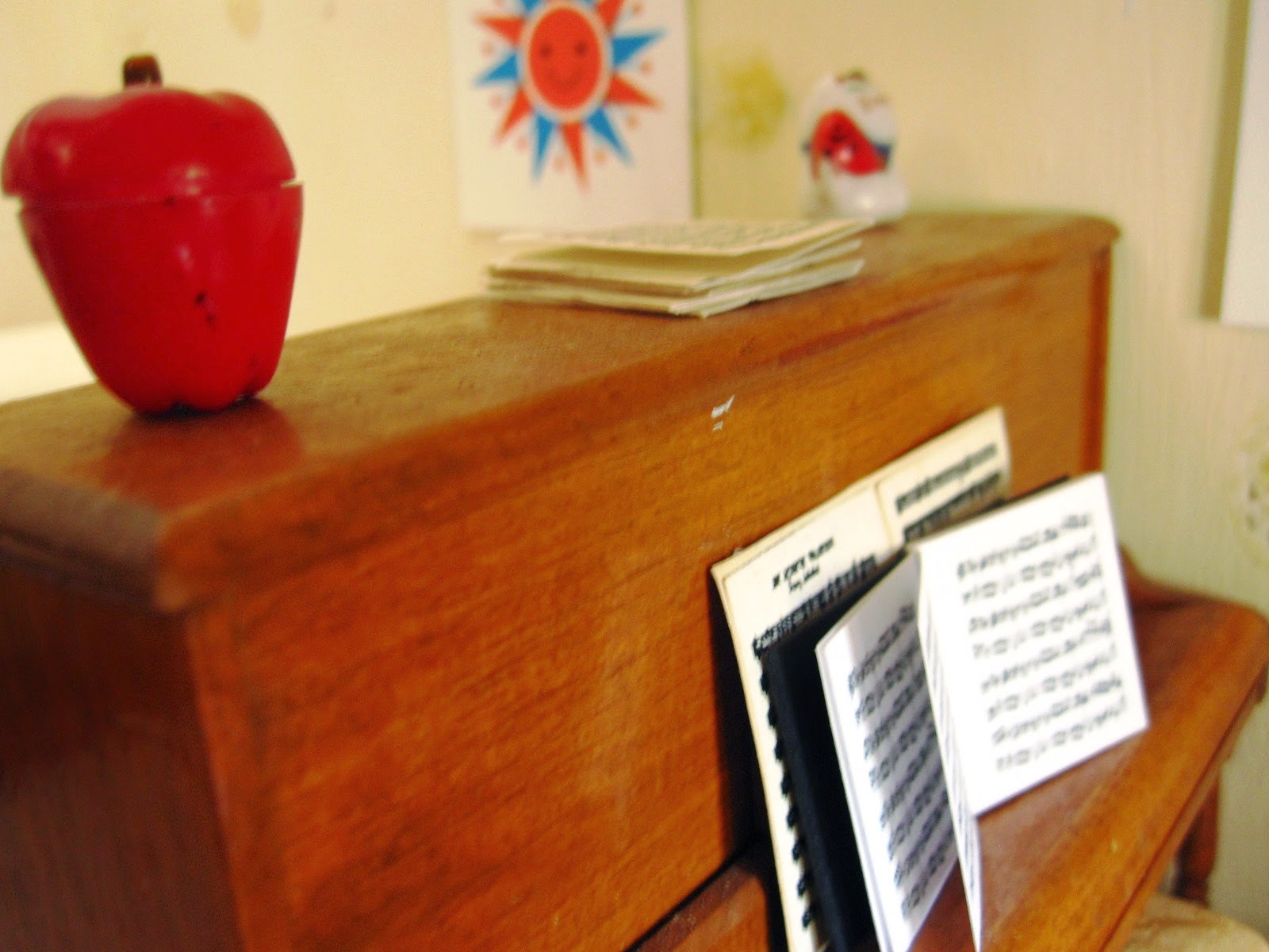 Modern dolls' house miniature piano with sheet music.