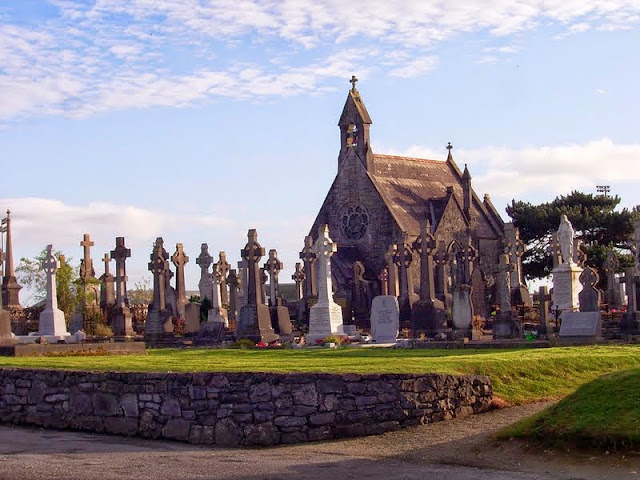 Irish cemetery - white and grey head-height celtic cross grave-markers / headstones, stone chapel,