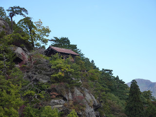 Photo over the side of the mountain with a temple building on the edge of a cliff