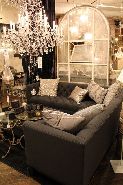 chandelier and black couch with platnum pillows