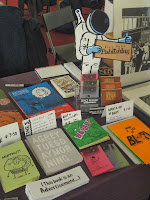 Photograph of Alex Hahn's books on sale at Thought Bubble and cartoon spaceman point of sale