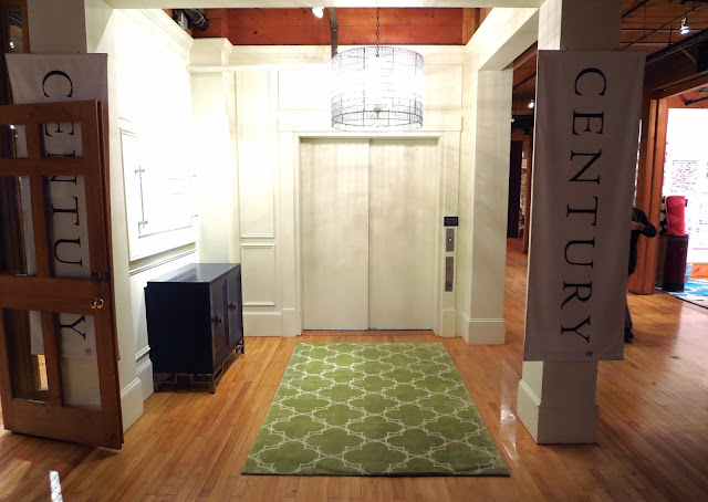 5' x 8' COCOCOZY Quatrefoil Rug in Apple Green at the elevator entrance to Century Furniture Showroom at High Point Market in North Carolina