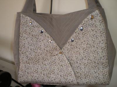 Bolsa de ombro em tecido de algodão liso e floral.