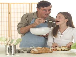 A father teaching daughter how to cook