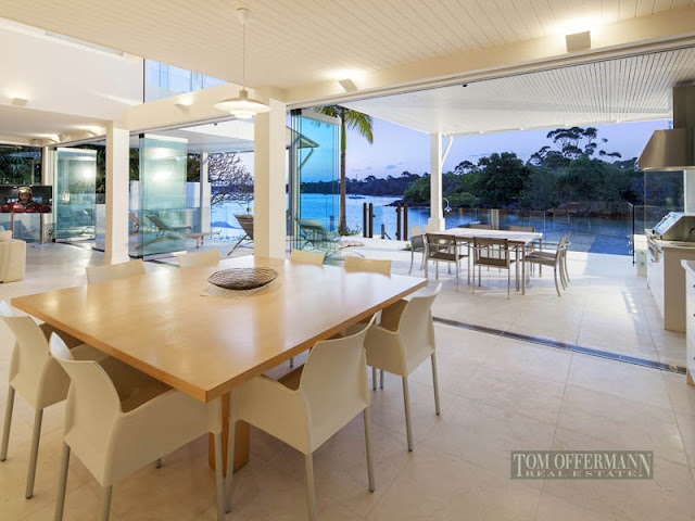 Photo of large open dining room with wooden dining table and modern chairs with the view of water