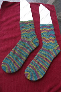 finished teal, green, yellow, and purple socks are shaped on sock blockers, which are laying on a maroon towel