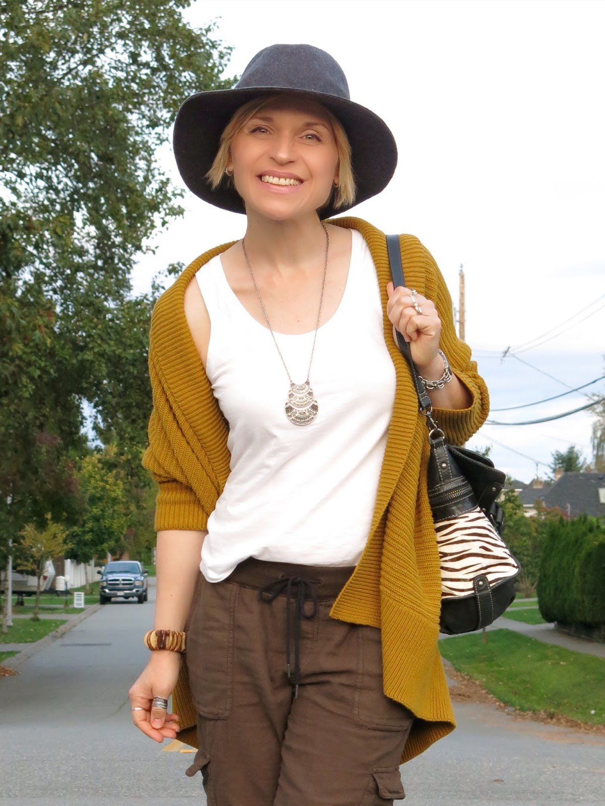 slouchy cargos with a drapey mustard-yellow cardigan, white tank, and floppy hat