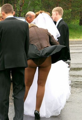 funny wedding picture: the wind blows her dress up