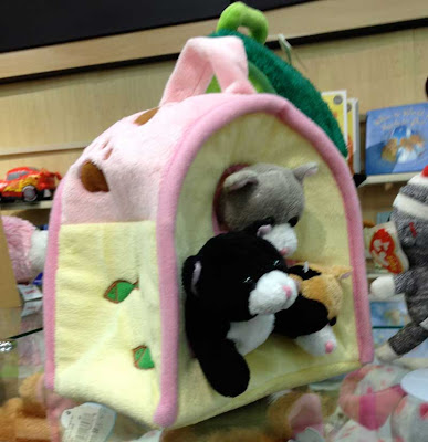 Three beanie babies with heads coming out of the wall of a pink and yellow tent-shaped bag
