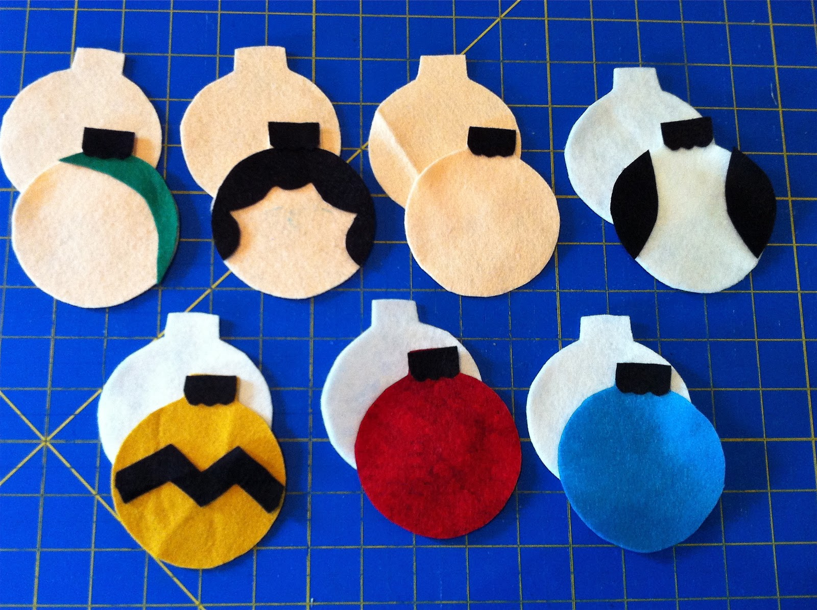 cut out the felt shapes from the ornament shape cut 6 peach 5 white and one each red yellow and blue each ornament will have a front and back main piece