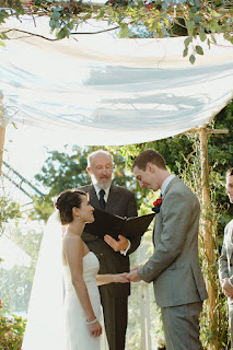 Kent Buttars, Seattle Wedding Officiant, watches as Jon places the wedding ring on Juanita's hand