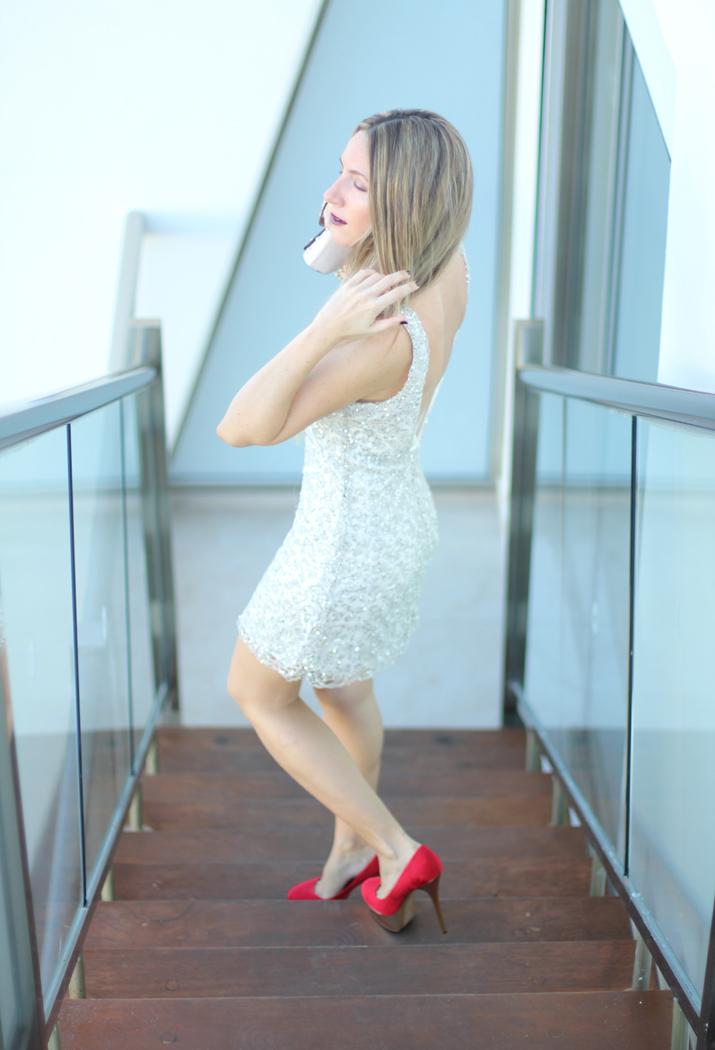 Idea de look para una cena de Navidad: vestido de encaje color plata y zapatos de tacón rojos