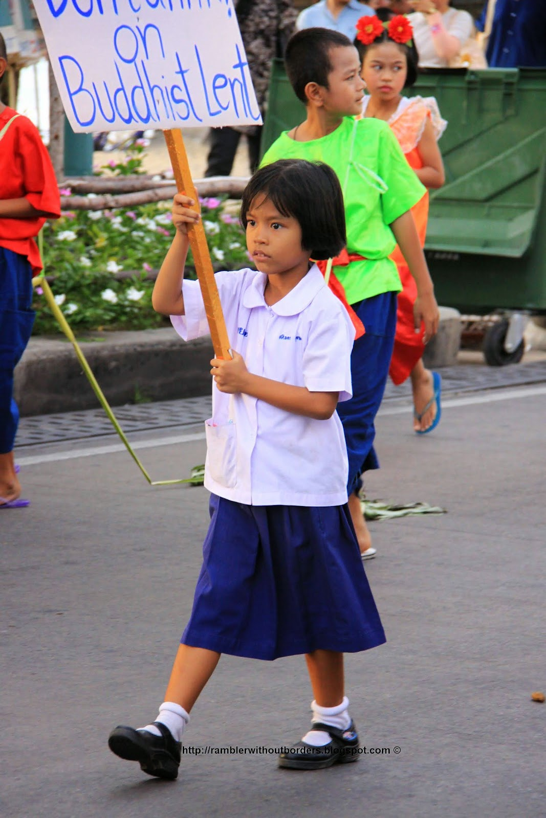"school girl in a parade holding the sign ""Buddhist Lent"""