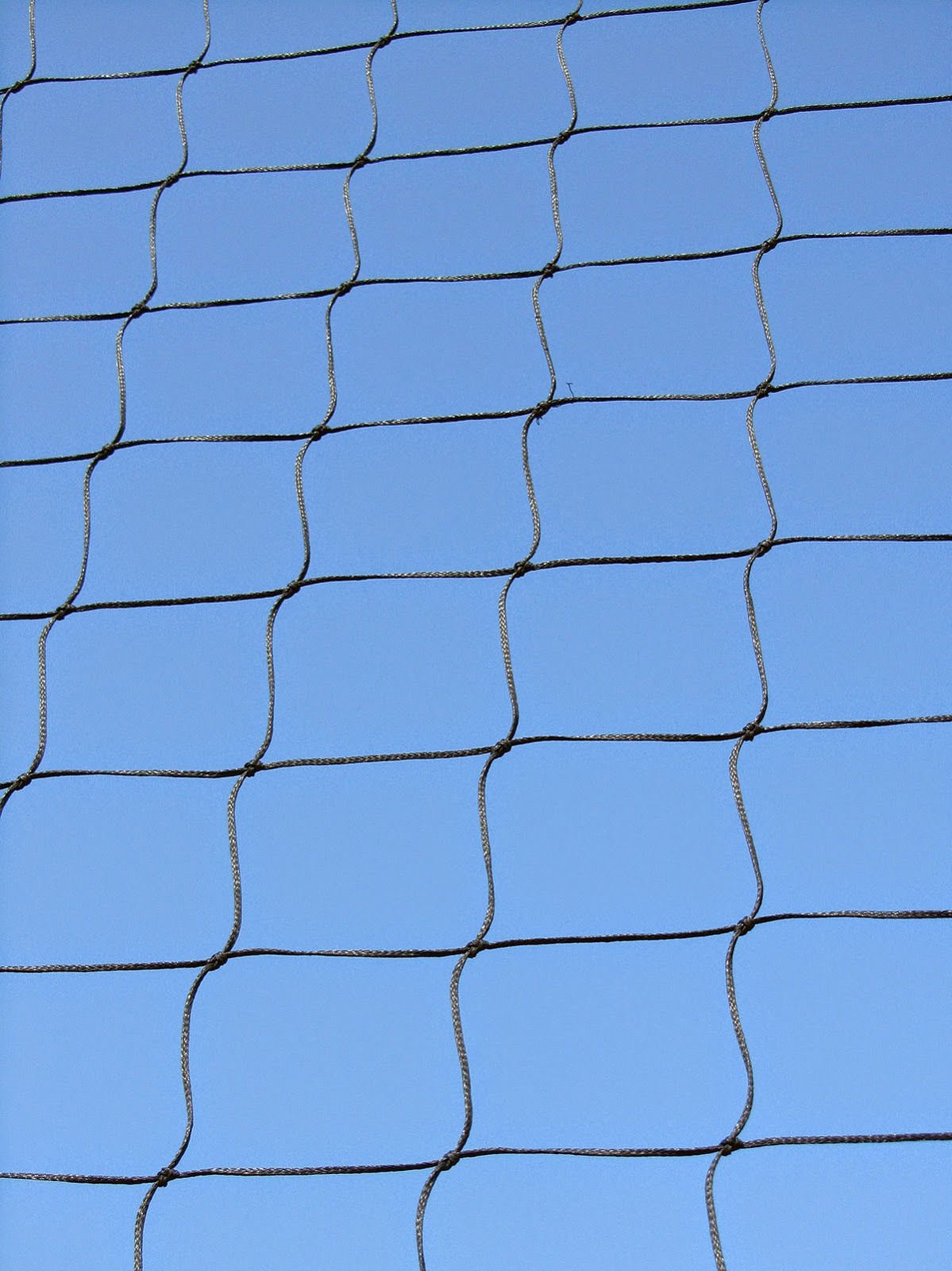 pattern of a soccer net against a blue sky
