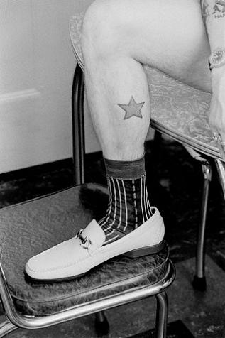 Black and white photo of a man's calf with simple star tattoo