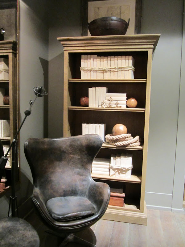 Room with grey walls and a light wood bookshelf and a modern grey leather armchair in the new Restoration Hardware
