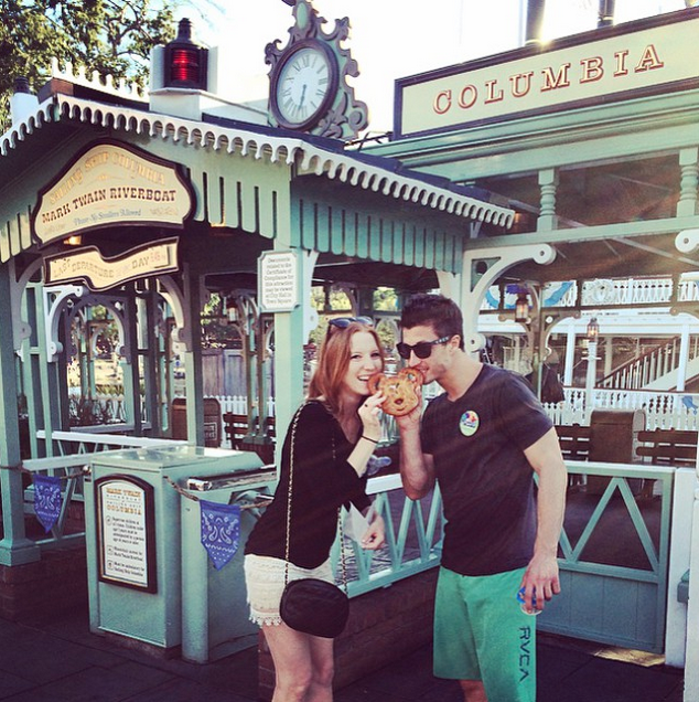 Man and woman eat pretzel at Disneyland