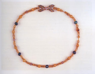 A Hellenistic Greek necklace, c. 300-200 B.C., in the polychrome style. The combination of gold, enameling, and colored glass beads shows the influence of the East—particularly Persia and Phoenicia. Length, 39 cm. Castellanies Collection, British Museum, London