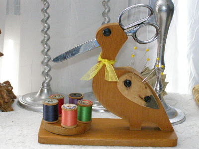 wooden duck that holds scissors, with spools of thread stored near its feet
