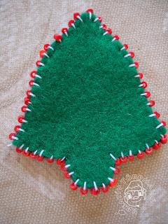 Szöveg: Oldalán gyöngyös karácsonyi csengő. Kép: Közelkép egy zöld sima csengőről, aminek a széleire piros gyöngyök vannak felvarrva fehér cérnával.