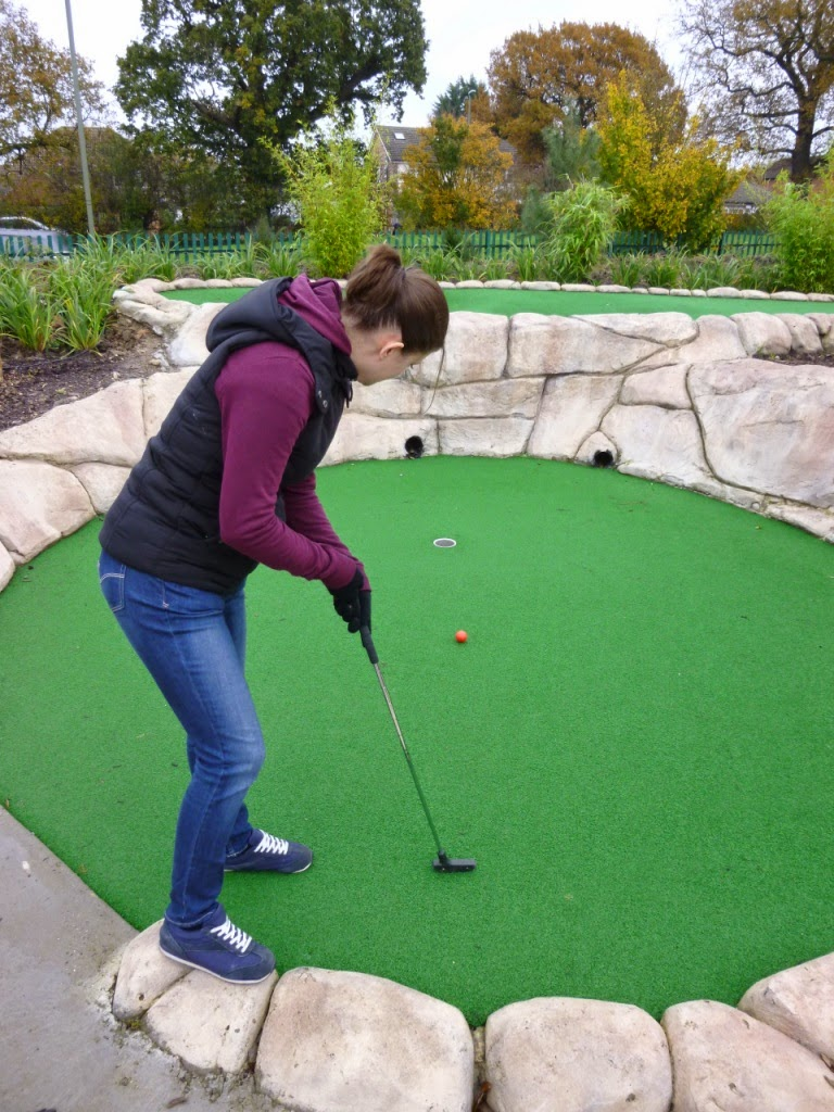 Emily Gottfried holing-out a long second putt at the Jungle Island Adventure Golf course at Horton Park Golf Club in Epsom